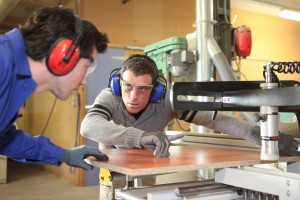 Håndverker og lærling ved maskin